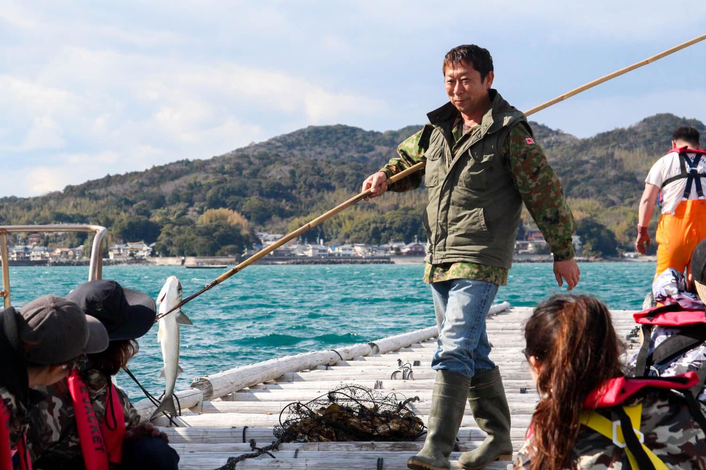 ボラを突き上げる漁師さん